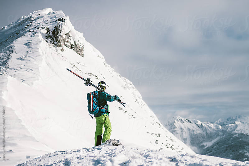 male skier standing alone on top of a snowcovered summit looking to the surrounding peaks by Leander Nardin for Stocksy United