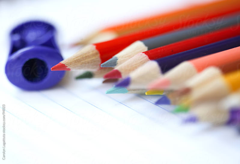 Sharp colored pencils and a sharpener on lined paper by Carolyn Lagattuta for Stocksy United