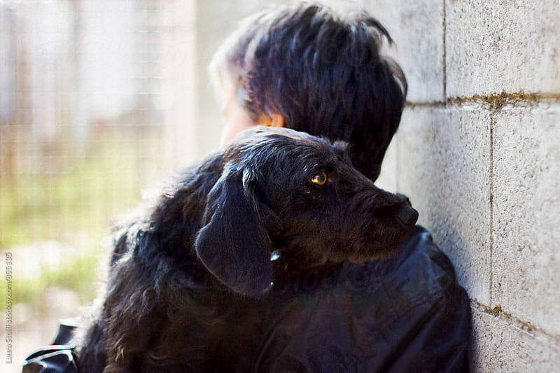 Woman embraces black dog, close up by Laura Stolfi for Stocksy United