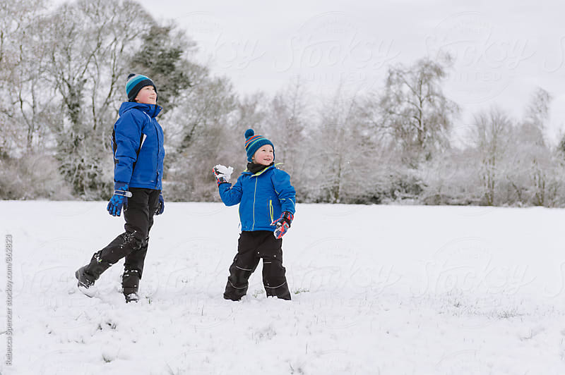 Brothers throwing snowballs by Rebecca Spencer for Stocksy United