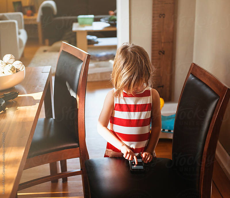 Cute preschooler girl looking sad playing with mobile phone by Rob and Julia Campbell for Stocksy United