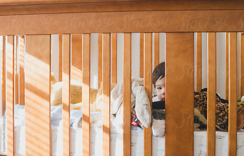 Little boy playing in wooden crib by Lauren Naefe for Stocksy United