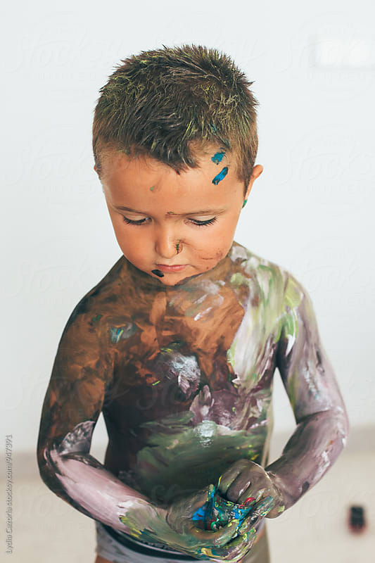 Playful child covered in paint by Lydia Cazorla for Stocksy United