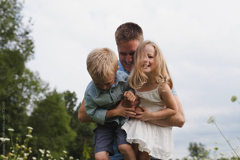 A father playfully picks up his son and daughter by Amanda Worrall for Stocksy United