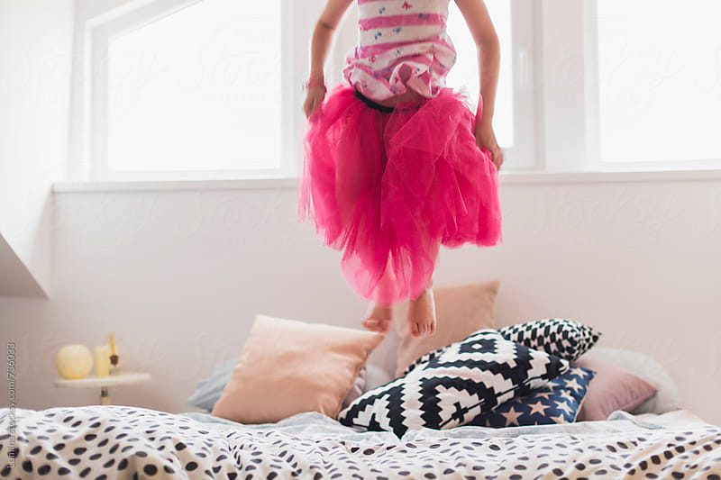 Girl in a Pink Skirt Jumping on Bed by Lumina for Stocksy United