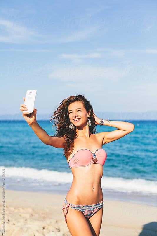 Beautiful woman taking selfie on the beach by Aleksandar Novoselski for Stocksy United