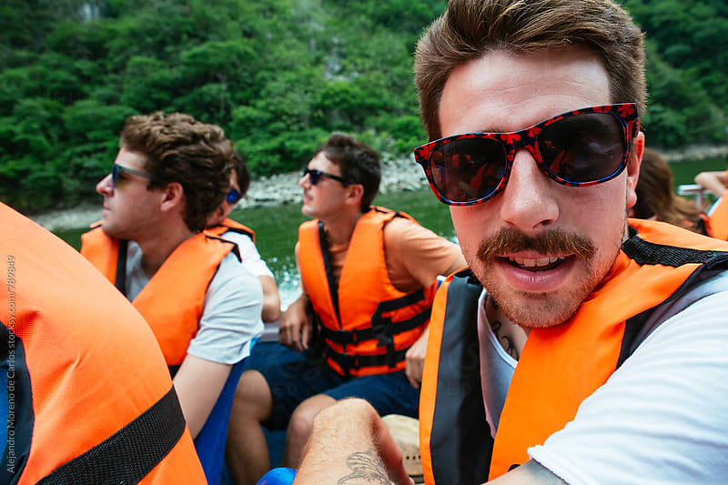 Close up of a young male wearing a life jacket in a boat on a lake during a holiday trip by Alejandro Moreno de Carlos for Stocksy United