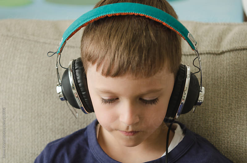 boy with headphones by Tomas Kraus for Stocksy United