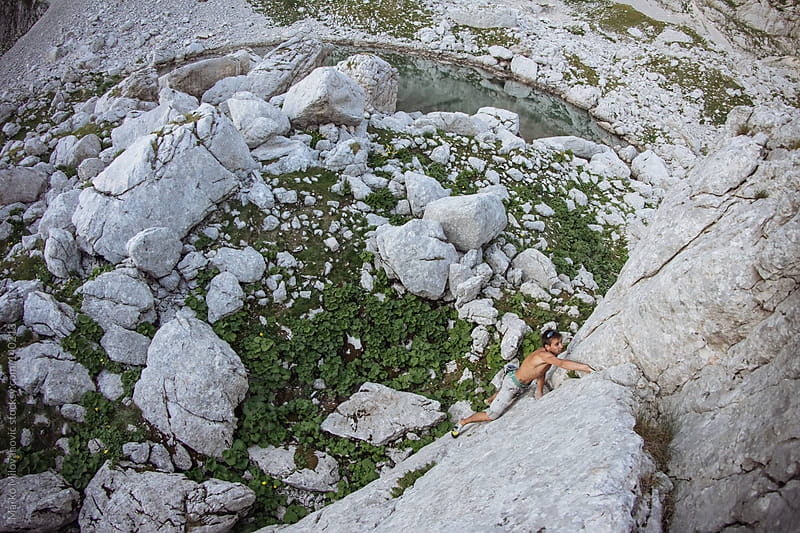 Young man climbing natural rock by Marko Milovanović for Stocksy United