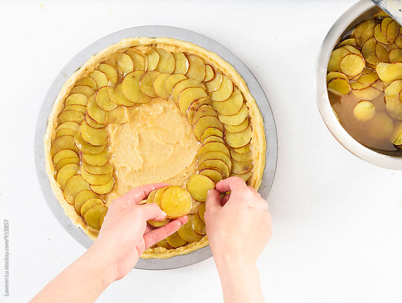 Hands putting potatoes slices on pastry in metal baking form by Lawren Lu for Stocksy United