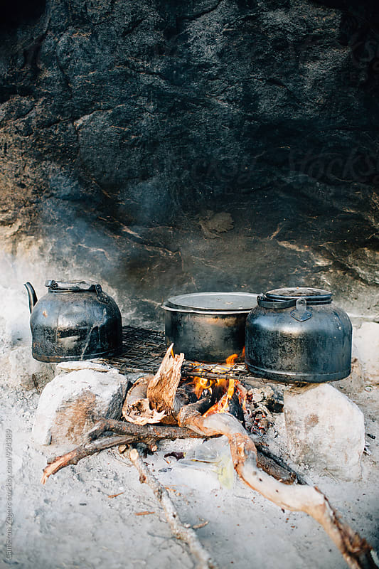 cooking over campfire in Tanzania by Cameron Zegers for Stocksy United