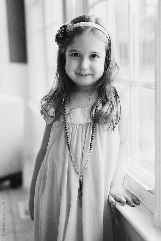 Portrait of a beautiful young girl standing by window in a dress by Jakob for Stocksy United