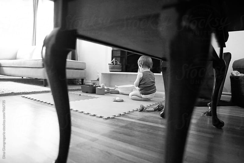 View Of Baby Playing With Toys In Livingroom by Dina Giangregorio for Stocksy United