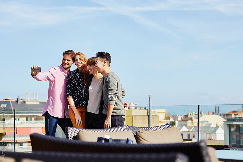 Happy Friends Taking Selfie On Hotel Terrace by ALTO IMAGES for Stocksy United