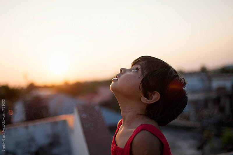 Little girl looking up to the sky at sunset by Saptak Ganguly for Stocksy United