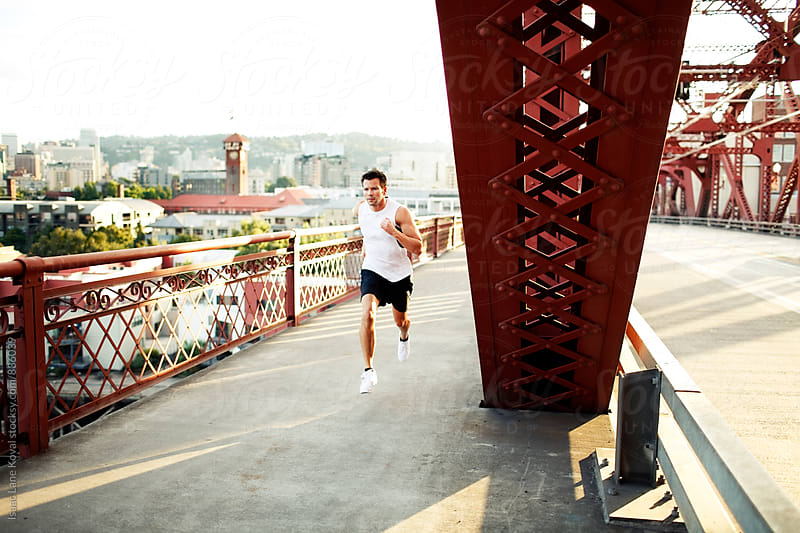 Man running on bridge at sunset by Isaac Lane Koval for Stocksy United