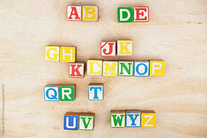 arranging vintage wooden blocks into the alphabet by Natalie JEFFCOTT for Stocksy United