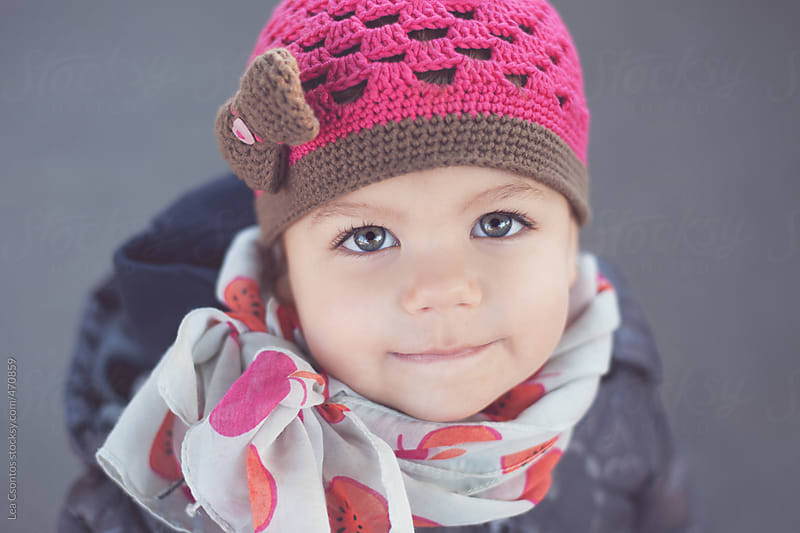 Sweet face of a toddler girl wearing scarf and a cute hat looking up by Lea Csontos for Stocksy United