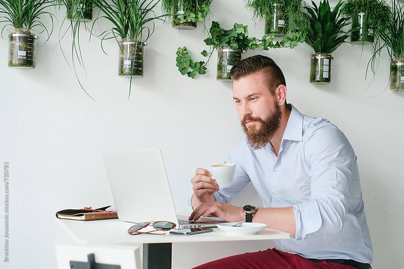 Man Drinking Coffee and Working on Computer by Branislav Jovanović for Stocksy United