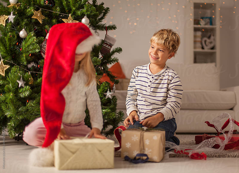 Kids Opening Christmas Presents at Home by Mosuno for Stocksy United