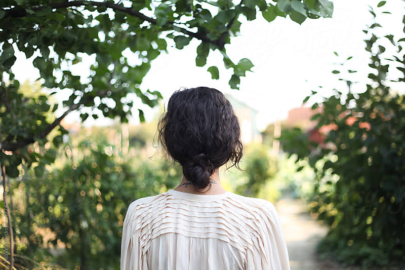 Woman standing in the garden, from the back by Marija Mandic for Stocksy United