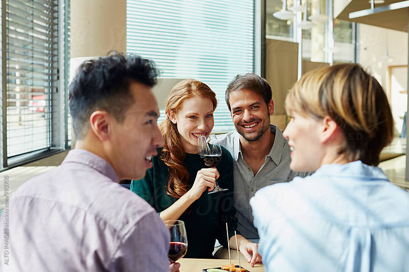 Couple Looking At Friends Talking In Restaurant by ALTO IMAGES for Stocksy United