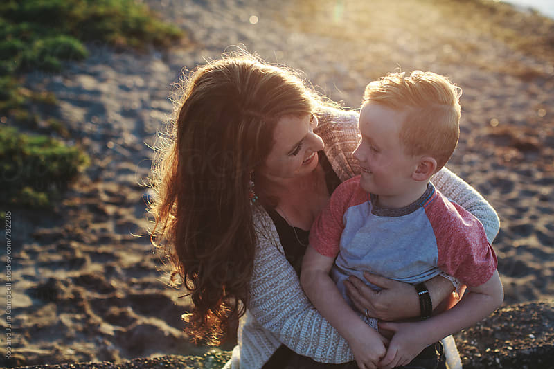 Happy young mom cuddling with son outside near water by Rob and Julia Campbell for Stocksy United