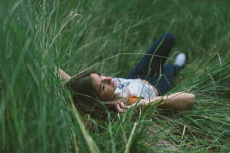 Young female in lying in a field by Douglas Robichaud for Stocksy United