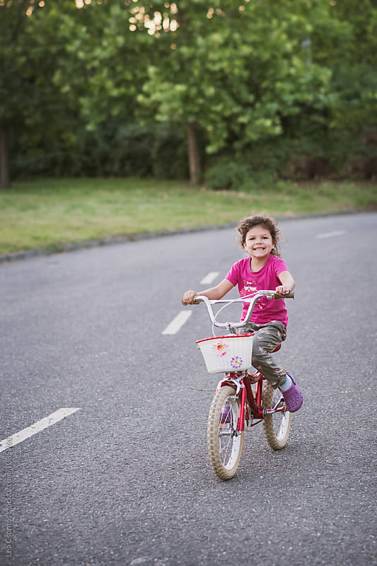 Happy young girl riding her bike by Lea Csontos for Stocksy United