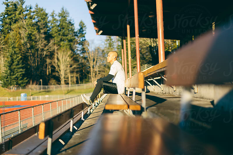 Athletic Man Sitting On Bleachers At Track And Field Stadium by Luke Mattson for Stocksy United