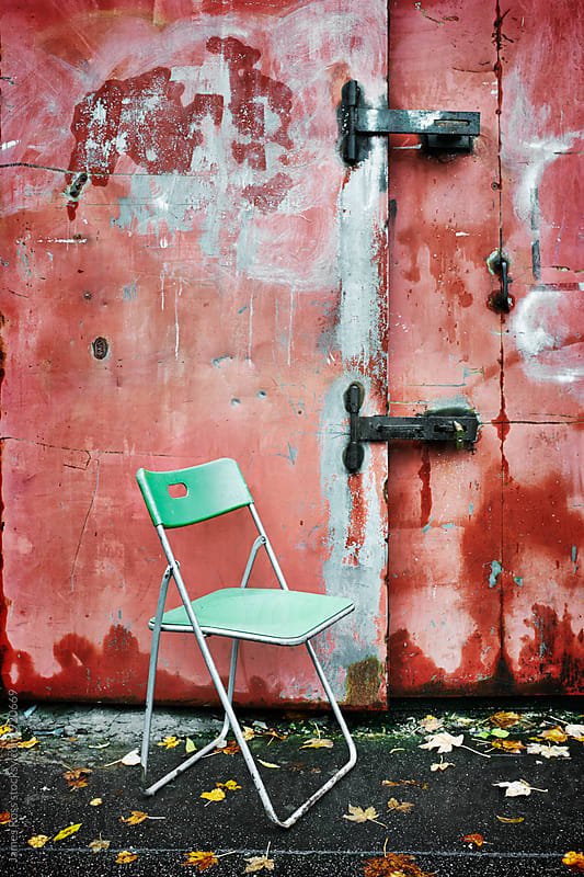A plastic chair by a painted metal gate by James Ross for Stocksy United