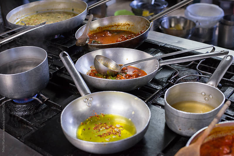 Variety of pans on a large hob by Mike Marlowe for Stocksy United