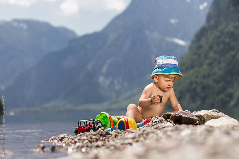 toddler playing in a lake by Leander Nardin for Stocksy United