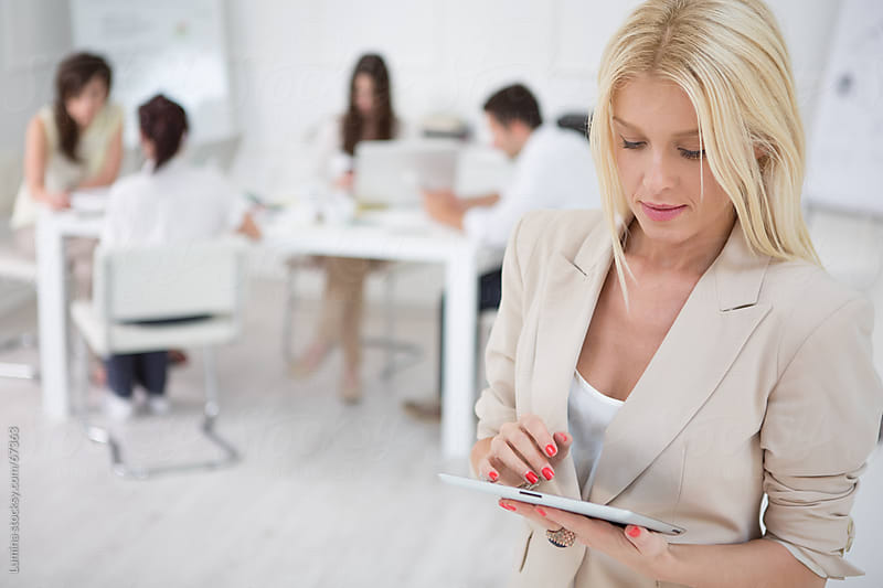 Businesswoman Using a Digital Tablet by Lumina for Stocksy United