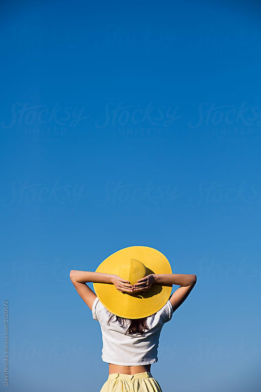 Back view of young girl in yellow sunhat against of blue sky by Danil Nevsky for Stocksy United