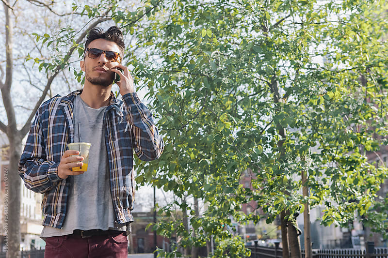 Casual Young Man Talking on Cell Phone by Joselito Briones for Stocksy United