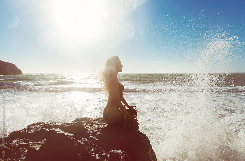 Young Woman Meditating by the Sea by VISUALSPECTRUM for Stocksy United