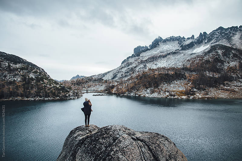 Female standing on rock above serene blue lake by Tari Gunstone for Stocksy United