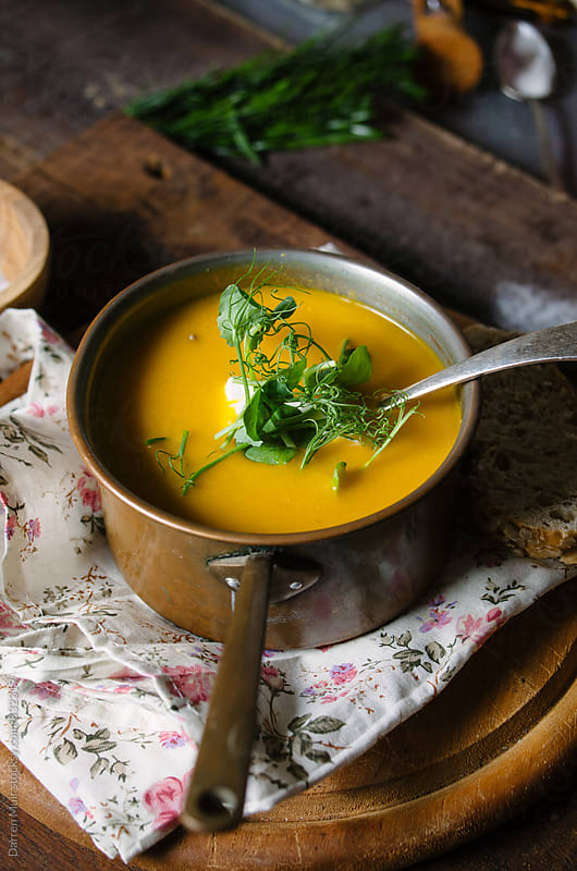 Carrot soup: a pot of carrot soup in a rustic wooden setting. by Darren Muir for Stocksy United