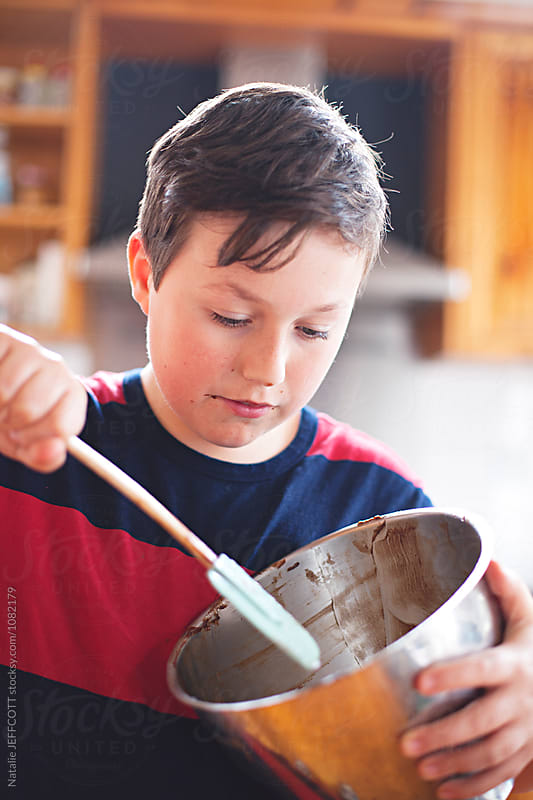 A young boy making a cake and eating the batter by Natalie JEFFCOTT for Stocksy United