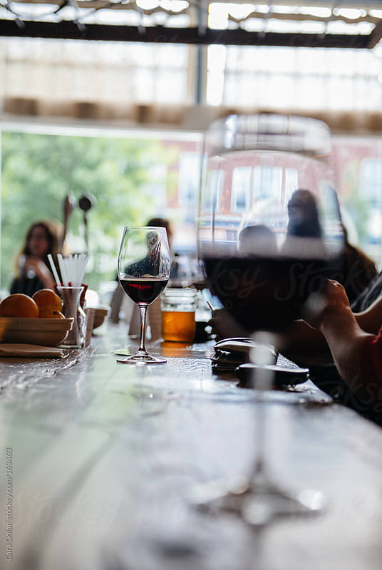 Red wine glasses at a restaurant bar by Cara Dolan for Stocksy United