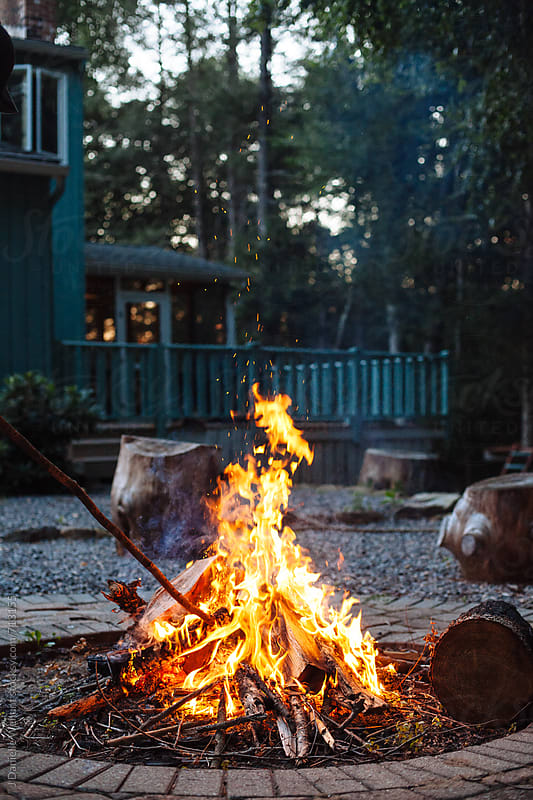 A bonfire in a back yard with house in background. by J Danielle Wehunt for Stocksy United