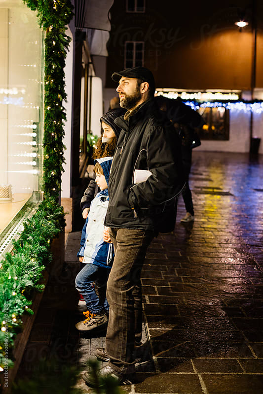 Family looking at a shopping window decorated with pine branches for Christmas by Beatrix Boros for Stocksy United