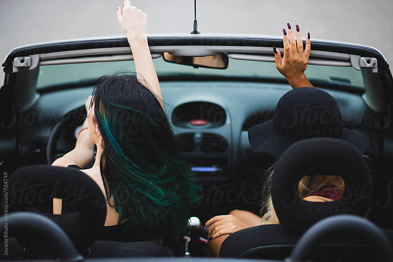 Happy female friends enjoying road trip in their cabriolet by Jovana Rikalo for Stocksy United