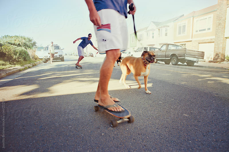 Men Skateboarding with Pet Dogs Running by Joselito Briones for Stocksy United