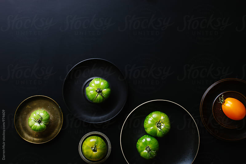 Heirloom tomatoes on dark background. by Darren Muir for Stocksy United
