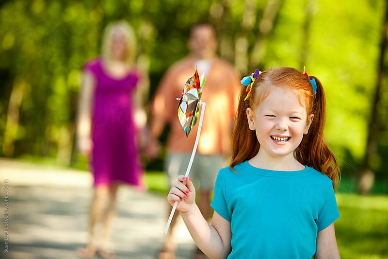 Park: Little Girl Having Fun Day Out with Parents by Sean Locke for Stocksy United