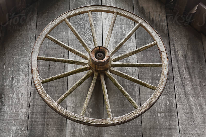 Old wagon wheel on front of a blacksmith shed in a forest by David Smart for Stocksy United