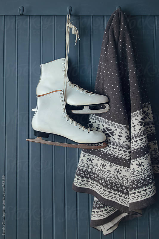 A pair of ice skates with blanket hanging on hook by Sandra Cunningham for Stocksy United