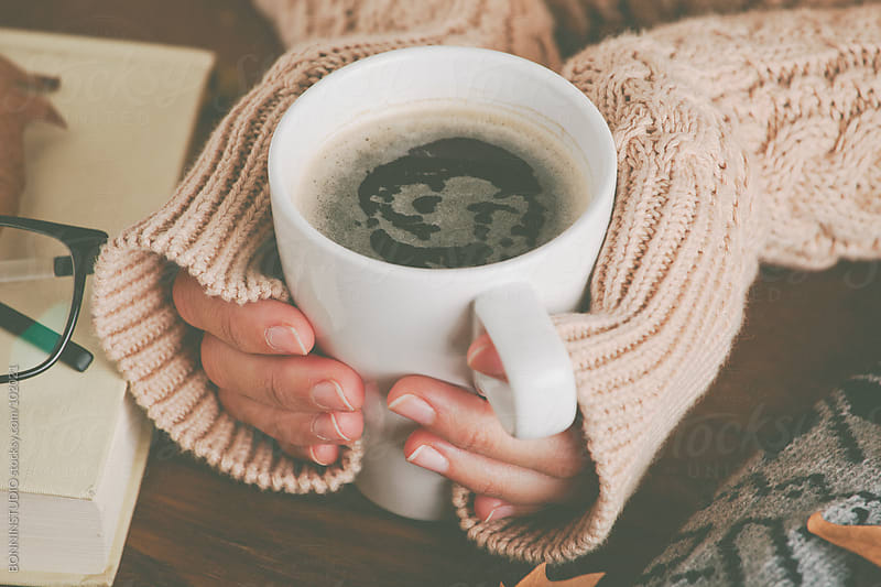 Cozy home. Woman warming up her hands with coffee mug. by BONNINSTUDIO for Stocksy United